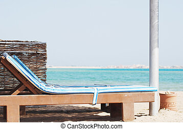 empty beach chair with straw sunshade at the sea