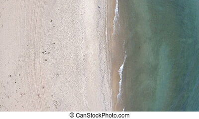 Empty beach. Top down, aerial view. Drone flies back. Lake...