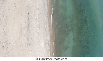 Empty beach. Top down, aerial view. Drone rise up above...