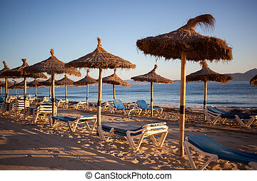 Empty beaxh with straw umbrellas on sunrise in Spain, ...