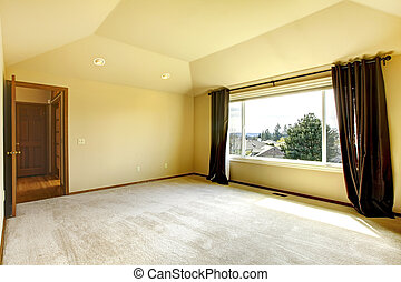 Brigth empy room with high vaulted ceiling and beige carpet floor. View of window with curtains