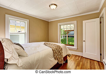 Empty bedroom interior with white bedding and hardwood floor.