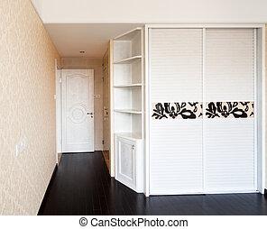 Empty bedroom with doorway and cabinet