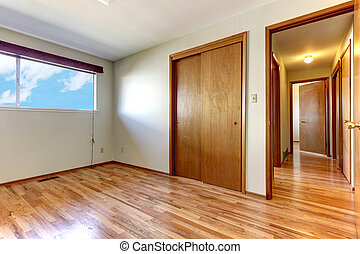 Empty bedroom with shiny hardwood floor.