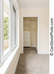 Empty bedroom with window and closet