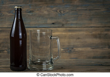 Empty beer bottle and glass on grunge wooden background