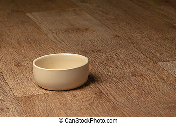 Empty beige cat and dog food bowl on the floor