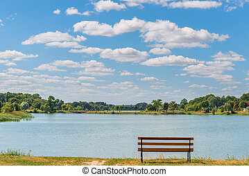 empty bench by the lake on a sunny day