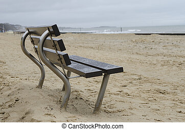 Empty bench by the sea on an overcast day