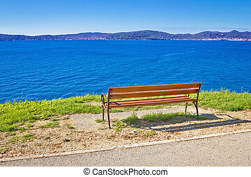 Empty bench by the sea