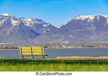 Empty bench facing an amazing view of a lake and mountain capped with snow
