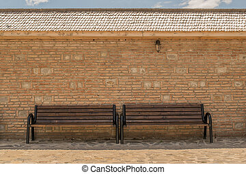 empty benches with brick wall background, wood tiles roof and vintage wall light fixture