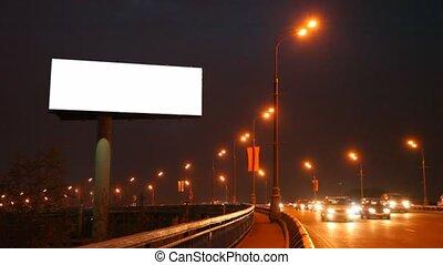 empty billboard near bridge with moving cars in night city