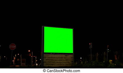 Empty billboard with chroma key green screen at night. Street lights and moving vehicle in the dark 4k