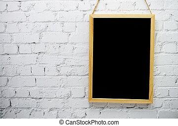 Empty black board on white brick wall background