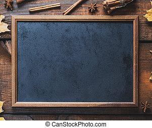 empty black chalk frame on brown wooden background