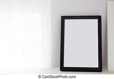 Empty black frame with place for text of on table. Scandinavian hipster style room interior.