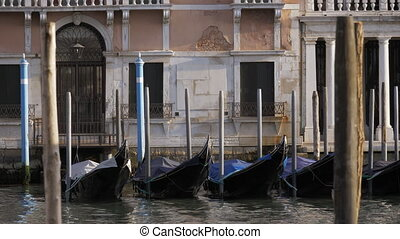 Empty black gondolas swaying on a pier close to the...