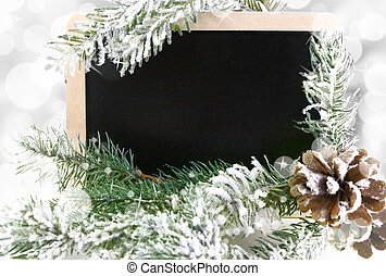 Empty blackboard with snowy Christmas tree and bokeh background