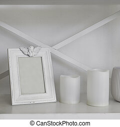 Empty blank white Wooden frame and white candles on wooden shelf