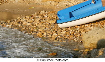 Empty blue-and-white fishing boat on the seashore. Waves with foam beat against the shore