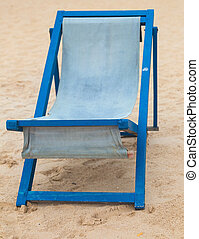 Empty blue deckchair at sandy beach