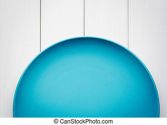 Empty blue plate on white wooden background. Top view with copy space