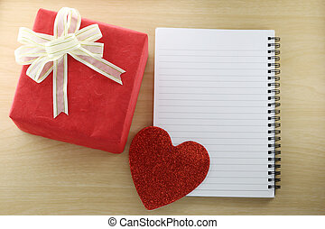 Empty Book and red gift box on the wooden floor.