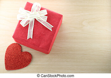 Empty Book and red gift box place near heart shape on the wooden floor.