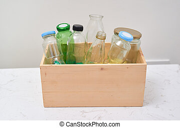 Empty bottles in wooden container on table.