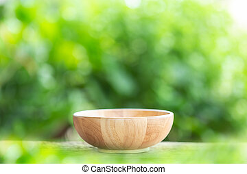 Empty bowl on wooden table with green blur light background