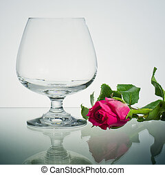 Empty Brandy glass and pink rose on glass