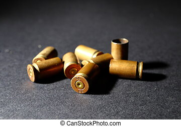 Empty bullet shell casings, on a black background, smoke