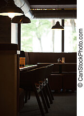 Empty cafe interior with wooden furniture and sofa
