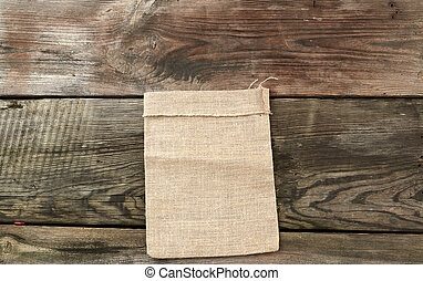 empty canvas gray bag on a wooden background from boards