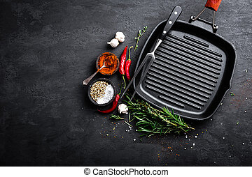 Empty cast-iron grill pan with ingredients for cooking on black background, top view
