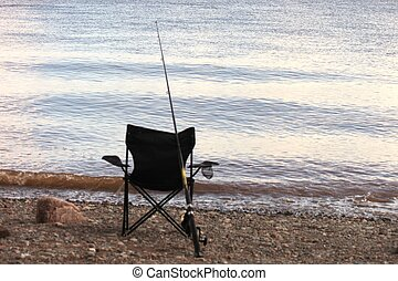 Empty black chair and fishing pole sitting on the beach with Bay of Fundy in foreground stock photograph