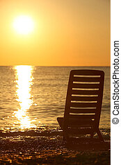 Empty chair stands sideways on sea-shore in the evening during sunset