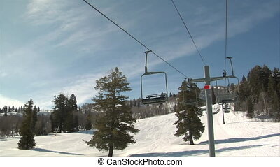 Empty chair zip by on chairlift above snowy slope