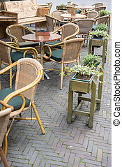 Empty chairs and tables in a street cafe