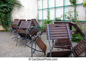Empty chairs and tables outside a street cafe