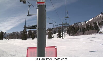 Empty chairs zip by on chairlift, skiiers below