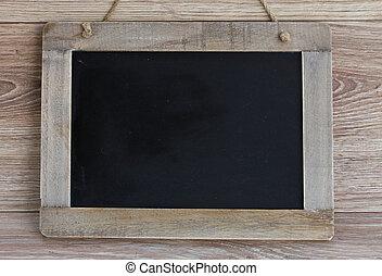 empty vintage black chalkboard hanging on wooden background
