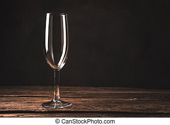 Empty champagne glass on a cozy atmospheric wooden background.