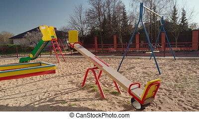 Empty children playground in square park in the center of city during quarantine by reason of coronavirus covid-19 virus threat. State of emergency. Pan shot