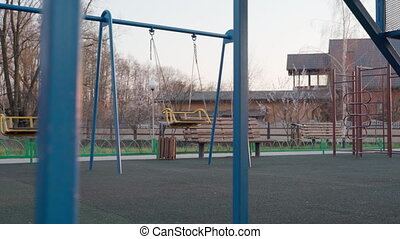 Empty children playground in square park in the center of city during quarantine by reason of coronavirus covid-19 virus threat. State of emergency