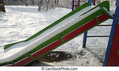 Empty children playground in winter. Snow covered childrens...