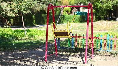 Empty children's swing in summer park
