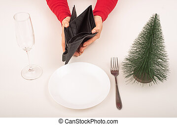 Empty christmas wallet. A woman is holding a purse with no money on an empty holiday table. The financial crisis during the holidaysempty, wallet, christmas, crisis, celebrations, finance, holding, money, problems, unhappy, new, sadness, women, year, opening, poor, holiday, bankruptcy, season, tree...