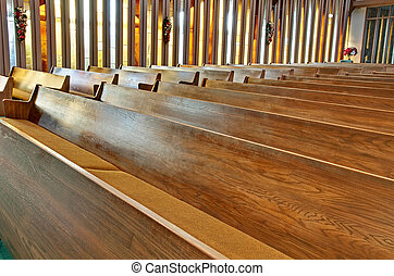 This stock image has rows of empty wooden church pews with sunlight filtering through the vertical stained glass windows.